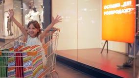 Seizoen van kortingen, berijden de gelukkige jonge geitjesvrienden in klantenkarretjes bij winkelcentrum voorbij winkelvensters stock video