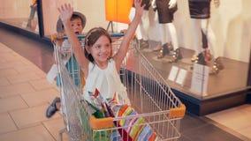 Seizoen van kortingen, hebben de lachende kinderen pret in het winkelen karretjes in wandelgalerij en gaan voorbij winkelvensters stock videobeelden