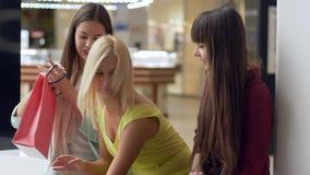 Seizoengebonden verkoop, gelukkige meisjes die bos van kleurendocument zakken houden die in winkelcentrum zitten stock footage