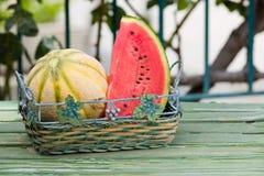 Seizoengebonden verse vruchten, watermeloen en rockmelon in mand op tuinlijst Stock Afbeeldingen