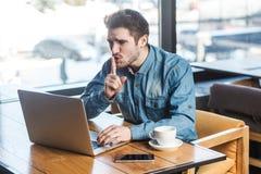 Seja quieto por favor! O retrato da vista lateral do freelancer novo farpado severo na camisa de calças de ganga está sentando-se imagens de stock