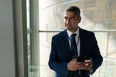 Sekcja biznesmen patrzeje oddalony i trzyma jego telefon komórkowego obraz royalty free