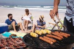 Sekcja mężczyzna robi grillowi przy plażą podczas gdy jego przyjaciele w tle obrazy stock