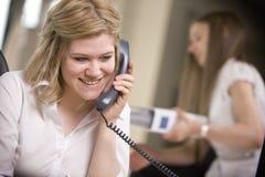 Sekretär, der Kenntnisse über dem Telefon nimmt Stockbild