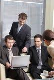 Sekretärumhüllung-Tasse Kaffee zu den jungen Geschäftsleuten im Büro Lizenzfreie Stockfotografie