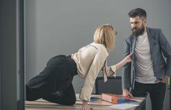 Sekretarka ciągnie kurtkę szef w biurze uwiedzenie i flirtować pojęcie, obrazy stock