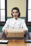 Sekretarka otrzymywa niespodzianki pudełko przy biurem Zdjęcia Stock