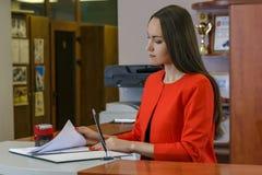 Sekretarka w czerwonym kostiumu stawia znaczek w przybywających wiadomościach biurowa praca, dokument kontrola Zdjęcie Royalty Free