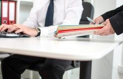Sekreterare och affärsman på kontoret Arkivfoto