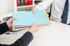 Sekreterare som sätter mappar i handen av en affärsman Royaltyfri Fotografi