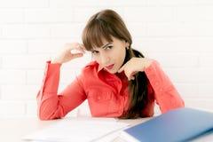 Sekreterare som sitter på skrivbordläsningdokument, förförelse royaltyfria bilder