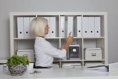 Sekreteraren tar en mapp från kabinettet Royaltyfria Bilder
