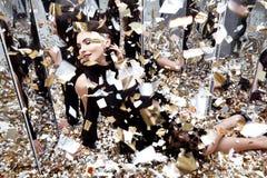 Seksowna ładna kobieta siedzi na podłoga z udziałem złoty cekinu gl Fotografia Stock