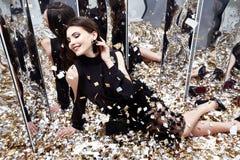 Seksowna ładna kobieta siedzi na podłoga z udziałem złoty cekinu gl Obrazy Stock