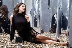 Seksowna ładna kobieta siedzi podłoga z udziałem złoty cekinu splendor f Zdjęcie Royalty Free