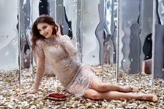 Seksowna ładna kobieta siedzi podłoga z udziałem złoty cekinu splendor f Obrazy Royalty Free
