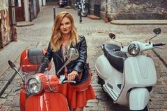 Seksowna blondynki dziewczyna jest ubranym elegancką odzieżową pozycję na starej ulicie z dwa retro hulajnoga zdjęcia stock