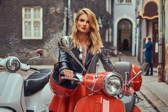 Seksowna blondynki dziewczyna jest ubranym elegancką odzieżową pozycję na starej ulicie z dwa retro hulajnoga obraz royalty free