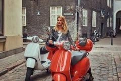 Seksowna blondynki dziewczyna jest ubranym elegancką odzieżową pozycję na starej ulicie z dwa retro hulajnoga obrazy royalty free