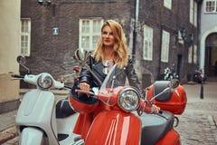 Seksowna blondynki dziewczyna jest ubranym elegancką odzieżową pozycję na starej ulicie z dwa retro hulajnoga zdjęcia royalty free