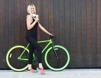 Seksowna blondynki dziewczyna w czarnej oprawie ubiera łasowanie lody na letnim dniu obok jaskrawego roweru załatwiającego Fotografia Stock