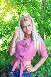Seksowna blondynki kobieta ono uśmiecha się wśród zielonych liści Zdjęcia Royalty Free