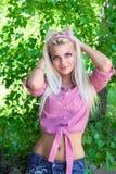 Seksowna blondynki kobieta ono uśmiecha się wśród zielonych liści Obraz Stock