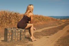 Seksowna blondynki kobieta siedzi na starej walizce plenerowej zdjęcie royalty free