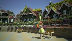 Seksowna blondynki młoda kobieta z barwionym tęcza parasolem chodzi, siedzi na ławce w kwiatu ogródzie, Śmieszny szczęśliwy marzy zbiory wideo