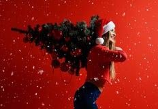 Seksowna Bożenarodzeniowa sprawność fizyczna sporta kobieta jest ubranym Santa kapeluszowego trzyma xmas drzewnego na jej ramiona fotografia royalty free