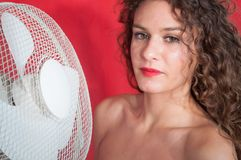 Seksowna brunetki dziewczyna z kędzierzawym włosy z chłodniczym fan fotografia stock