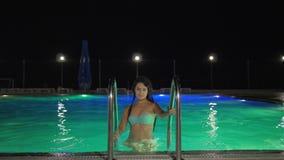 Seksowna ciało młoda kobieta w swimsuit komesie z barwionego wodnego mienia drabina basen w wieczór zdjęcie wideo