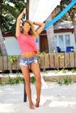 Seksowna dębna kobieta w okularach przeciwsłonecznych pozuje na plaży Zdjęcia Royalty Free