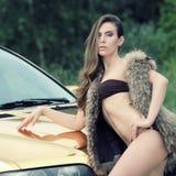 Seksowna dama blisko złotego samochodu Zdjęcia Royalty Free