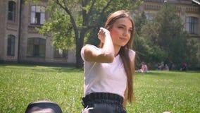 Seksowna dama siedzi na trawie w parku w dniu, oglądający przy kamerą, ono uśmiecha się, relaksuje pojęcie zbiory wideo