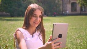Seksowna dama siedzi na trawie w parku w dniu, wideo wzywał pastylkę, relaksuje pojęcie, komunikacyjny pojęcie zbiory