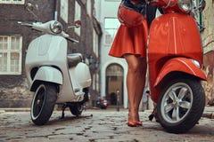 Seksowna dziewczyna jest ubranym elegancką odzieżową pozycję na starej ulicie z dwa retro hulajnoga zdjęcia royalty free
