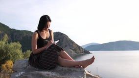 Seksowna dziewczyna pisze w notesie siedzÄ…cym boso wysoko na skale nad morzem zdjęcie wideo