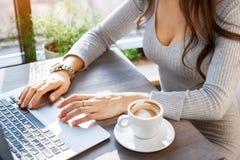 Seksowna dziewczyna pracuje na laptopie w kawiarni Zdjęcia Stock