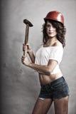 Seksowna dziewczyna w zbawczego hełma mienia młota narzędziu zdjęcie royalty free