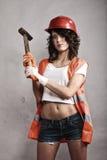 Seksowna dziewczyna w zbawczego hełma mienia młota narzędziu fotografia royalty free
