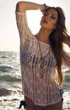 Seksowna dziewczyna z ciemnym włosy w bikini pozuje na zmierzch plaży Fotografia Stock