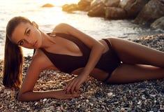 Seksowna dziewczyna z ciemnym włosy w bikini pozuje na zmierzch plaży Zdjęcie Royalty Free