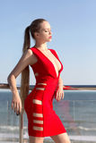Seksowna dziewczyna z długie włosy w czerwonej sukni na tle hałaśliwie morze Dziewczyna w czerwonej sukni na tle morze Fotografia Royalty Free
