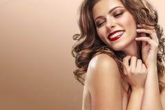 Seksowna dziewczyna z długim i błyszczącym falistym włosy Piękny model, kędzierzawa fryzura na pomarańczowym tle zdjęcia royalty free