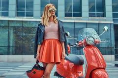 Seksowna elegancka blondynki dziewczyna jest ubranym czerwoną spódnicę i skórzana kurtka czarni okulary przeciwsłoneczni i, trzym obraz royalty free