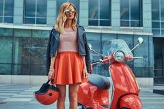 Seksowna elegancka blondynki dziewczyna jest ubranym czerwoną spódnicę i skórzana kurtka czarni okulary przeciwsłoneczni i, trzym zdjęcia stock