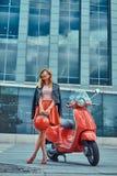 Seksowna elegancka blondynki dziewczyna jest ubranym czerwoną spódnicę i skórzana kurtka czarni okulary przeciwsłoneczni i, trzym obrazy stock