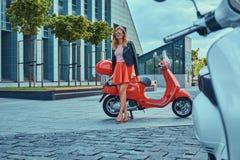 Seksowna elegancka blondynki dziewczyna jest ubranym czerwoną spódnicę i skórzana kurtka czarni okulary przeciwsłoneczni i, trzym zdjęcia royalty free