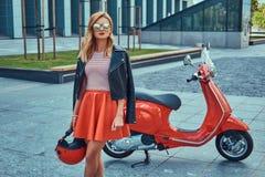 Seksowna elegancka blondynki dziewczyna jest ubranym czerwoną spódnicę i skórzana kurtka czarni okulary przeciwsłoneczni i, trzym fotografia stock